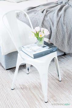 Die Farbe macht's! In Weiß wirkt der kühle Metallstuhl gleich ein bisschen femininer. Auch ein netter Bruch: Zarte pastellfarbene Tulpen finden in einem maskulinen Whiskey-Glas Platz.