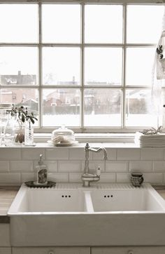 White kitchen with double farmhouse sink - Window over the sink - White tile backsplash