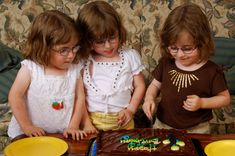 Triplets cutting birthday cake