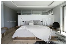 FourOnC Cape Town. Interiors by Del Fante Design Seaside bedroom on soft greys and whites on oak shelf bed with all black wegner lounge chair