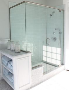 I lovethe idea of shelves for the towels in my bathrooms - blue gray glass shower tile brick pattern carrara marble seat penny tile floor walls molding white vintage canisters Glass Tile Shower, Blue Glass Tile, Blue Subway Tile, Glass Tiles, Tile Showers, Glass Bathroom, Half Glass Shower Wall, Glass Showers, Bathroom Marble
