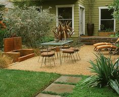 The main patio of coral pebbles features an outdoor fireplace and rich planting in blues, oranges and silver.