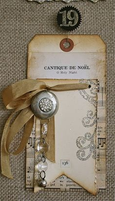 Sepia Tone Tag...made from old music sheets and finished with silky ribbon & bling.