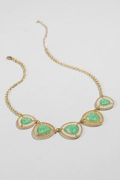 "Update your look with this one of a kind necklace!  Glistening mint stones are surrounded by white & iridescent beads & set within a golden triangle medallion.  Wear this with a formal dress & gold heels for a classic look.<br /> <br /> - Finished with a lobster claw clasp<br /> - 18.5"" length<br /> - 3.5"" extension<br /> - Lead & nickel free<br /> - Imported"