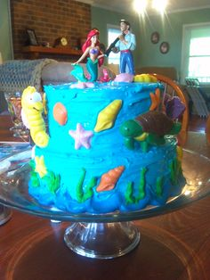 little mermaid birthday cake- made using 4 round cake pans (2 lg 2 small). decorated with candies made from molds (ac moore). larger sea creatures are lollipops made from molds. the sticks secured them in the cake layers. figurines from the disney store.