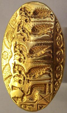 """Gold signet ring, the largest from the Mycenaean world, found in Tiryns, but made by a Minoan workshop (15th c. BCE). A procession of lion-headed """"daemons"""" offering libation jugs to the seated goddess who raises a ritual vessel: the sun wheel & the crescent moon are in the sky"""