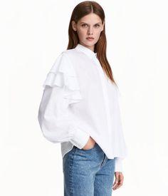 Wit. Een wijde blouse van geweven katoen met dubbele volants bij de schouders en…