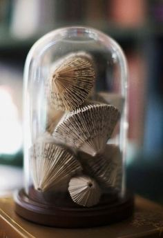 Ornaments made from the pages of old books.....a glass dome is the perfect way to protect and display these gorgeous creations!