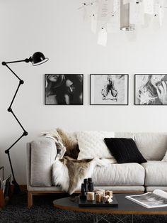 Sala de estar com tapete escuro, sofá com pés de madeira e estofado cinza claro, pelego decorativo, mesa de centro com tampo preto, luminária de canto preta, quadros na parede e lustre com papeis. Dicas e Inspirações de Mantas para Sofá