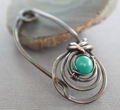 Copper shawl pin or scarf pin in a woven round design and turquoise stone