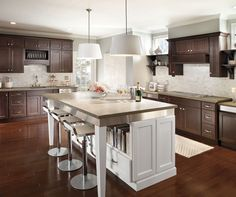 Ample island seating and contrasting finishes make this Homecrest Hershing kitchen the center of the party. New Year's Eve entertaining is guaranteed to go smoothly with optimal storage behind the dark cherry cabinets in Buckboard and stylish open shelving on the kitchen island in White.