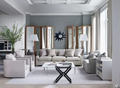 Bespoke folding screens flank a 1950s Line Vautrin mirror in the living room, whose walls are painted in Benjamin Moore's Silver Lake gray | archdigest.com