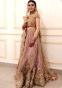 Sona Memon took the Internet by a storm with her bridal look in a Tena Durrani outfit. She wore a lilac and gold lehenga set with an off-shoulder blouse with firoza details. Her neatly set hair edgy jewellery and the dewy makeup look blew our minds. Gold Lehenga, Raw Silk Lehenga, Bridal Lehenga, Pakistani Wedding Dresses, Pakistani Dress Design, Pakistani Outfits, Indian Outfits, Pakistani Clothing, Punjabi Wedding