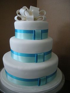 White cake with blue ribbons and white bow by A Sweet Design