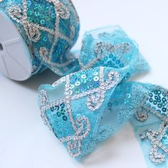 Organza and Sequin Trim Ribbon in Turquoise and Silver - 2.5in. x 10 yd  Get silver wedding decorations like this gorgeous turquoise organza trim ribbon with silver accents and sequins. Turquoise and green sequins make this sparkling jewel trim the perfect accent to add bling to bouquets, vases, gift wrap, and more!  #afloral