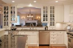 Classic white kitchen with arched valance framing view to the dining room. Double entry glass mullion cabinets allow access to dishes from kitchen and dining room White Granite Kitchen, Granite Counters, Upper Cabinets, Kitchen Cabinets, Kitchen Dining, Dining Room, Classic White Kitchen, Stainless Steel Appliances, Dishwashers