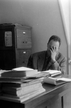 Albert Camus face palming and laughing.