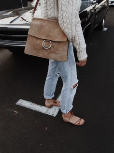 cream cable knit sweater + faded ripped blue jeans + strappy brown sandals + camel suede shoulder bag // @kayliemal
