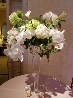 Tall arrangement of white phalenopsis orchids, hydrangea, calla lilies.  In bloom, ltd.