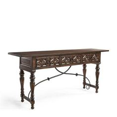 Marrying the masculinity of dark mahogany with the feminine swoop of an iron stretcher and scroll embellishments, the Aurora Console has two large drawers    behind a row of six carved geometric stars.            Crafted of solid wood                Warm mahogany finish                Carved drawer fronts                Two wide and deep drawers                Aged iron finish on curved metal stretcher                Mediterranean design    Assembly required
