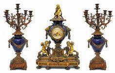 Excepcional Terno Francês, em porcelana azul cobalto, possivelmente de Sévres, e bronze de delicada e definida fundição. Grupo composto de par de candelabros para seis velas para cada uma das peças e relógio central da manufatura L. Barbaster, Paris. Relógio 68 cm. Candelabros 67 cm.