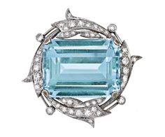 AQUAMARINE AND DIAMOND BROOCH  The emerald cut aquamarine weighing approximately 40.00 carats is claw set within a wreath set with single and round brilliant cut diamonds, mounted in platinum and 18ct white gold,