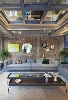 sala de esatr decorada com sofá grande cinza, parede rústioca com tijolos a vista, espelho redondo na parede com quadros vintage e modernos, mesa de centro grande e baixa