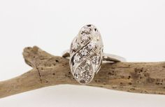 Cast in 14k white gold, this vintage diamond ring has a beautiful oval shaped cluster mounting with sparkling diamonds and fabulous 1960s