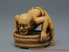 Man in a tub biting a coin. Ivory Netsuke. Inscribed OKATOMO. 19th C. 小判をくわえる人物 岡友銘有 象牙 根付