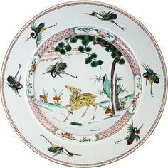 Très grand plat décoré d'un cerf en porcelaine de Chine de la Compagnie des Indes d'époque Kangxi Décoré dans les émaux translucides de la palette de la famille verte, avec six grues sur l'aile bordant une frise d'oeufs de poissons. Sur le marli, quatre cartouches altèrent avec une frise de croisillons.
