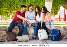 Full length portrait of a bunch of college students looking at a tablet computer and having fun - stock photo