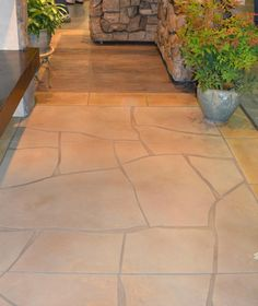 """The floor is a concrete overlay. In front of the islands it is stamped to look like hard wood. In front of the fireplace the concrete mimics flagstone. Each section is bordered by """"tiles""""."""