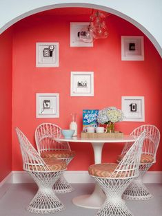 An arched nook cut into a light blue wall has been painted coral orange. The bright wall displays six framed actual cameras. A round, white dining table and its four cushioned wire chairs create a fun and cozy breakfast nook. Decor, Interior, Home Decor, Bedroom Door Design, Dining Room Contemporary, Bedroom Decor, Bedroom Colors, Interior Design, Breakfast Nook