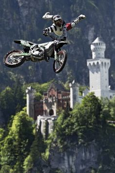 Motor Flying . . . Red Bull X-Fighter jumps in front of the Neuschwanstein Castle, Munich, Germany.