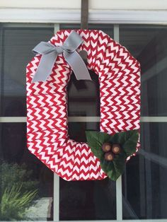 Chevron ribbon wrapped block O wreath. Made with red and white ribbon, grey bow, hand-painted buckeyes, and buckeye leaves. Finished product