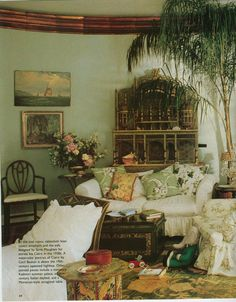 This oval room is her private study. A departure for the bright colors of the other rooms, has copper moldings & is painted a soft green. The furniture is slipcovered in white cottons.