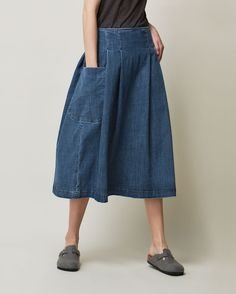 Full, pleated skirt, resting neatly on the hips, in a weighty, supple, indigo-dyed denim - washed for a lighter shade of indigo. Two large and deep patch pockets.