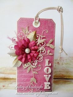 tag using memory box flower die, large ruby colored flower, pearl button center.  good idea for birthday card or valentines