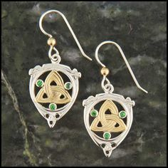 These unique Celtic earrings are made with a Sterling Silver frame, 18K Yellow Gold triquetra's or trinity knots, set with three Tsavorite Garnets in each earring.