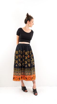 heavily embroidered midi skirt. folk motif. elastic waist. black with wide red hem.  measurements (while flat, multiply by 2 for exact measurement) : bust: n/a waist: 15 - 19 hips: open length: 34  tag: mixit, 100% cotton, size medium fits like: medium - large condition: amazing vintage condition! (accessories not included) model is 59 and measures 35 x 28 x 40 and usually wears a medium. please email with ANY questions!!!  shop updates / previews on instagram @gemandarrow