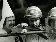 A black officer comes forward to protect KKK member from protesters, (1983)