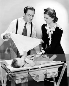 American actors William Powell (1892 - 1984) and Myrna Loy (1905 - 1993), as Nick and Nora Charles, changing their baby's nappy, in a publicity still for 'Another Thin Man', directed by W. S. Van Dyke, 1939.