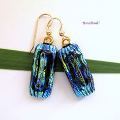When you see these unusual, one-of-a-kind handmade dichroic fused glass dangle earrings, you might think of the deep forest. These long rectangular earrings are made from a a layer of textured dichroic glass in blue, black, green and gold layered with a brilliant dichroic glass rod in the center.