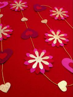 Mobile med 15 blomster og hjerter i rød, pink og præget guld på guldsnor. Smuk i vinduet eller hængende ned fra loftet. Se mere på www.jannielehmann.dk