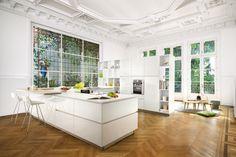 Nouveauté 2016 - Cuisine Design - Laque brillante - Strass Eolis. Dans une somptueuse pièce au fabuleux plafond mouluré et à la verrière des plus charmantes, brille une cuisine design et sur mesure, d'un blanc everest immaculé. Elle possède d'immenses possibilités de rangement cachés derrière ses portes design ou exposés dans les niches de sa bibliothèque intégrée.  Son plan de travail est prolongé par un plan snack coloris bois pour effet contrasté élégant.