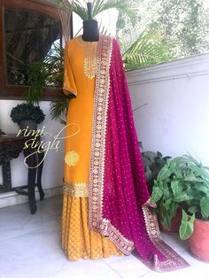 """""""Shine brightly"""" Turmeric yellow georgette sharara teamed with a dark plum dupatta with gota hand embroidery. There is gota hand embroidery on the neckline, sleeve and the kurta edge. Available exclusively at Rimi Singh Studio A 999 Sushant Lok 1 Gurgaon Pakistani Dresses, Indian Dresses, Indian Outfits, Indian Attire, Indian Ethnic Wear, Ethnic Style, Asian Fashion, Ethnic Fashion, Sharara Designs"""