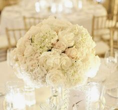 Low cylinder vase filled with cream hydrangeas, ivory roses, ivory spray roses, and white tulips; surrounded by clear fluted votives