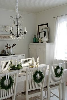I love the wreaths on the chairs, and all of the  white.