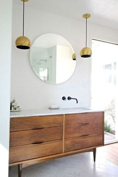 Stunning mid century bathroom console with round mirror and gold hanging lamps
