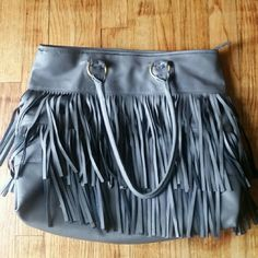Gray Fringe Tote Bag This bag in great condition and has a lot of space inside! It is gray with gold details , the fringe is gray on one side and black on the other side.   Inside there's a bag with a zipper and two spaces to put your cellphone in! Black interior 1 ft. 1 inch tall by 1 ft. 3 inch long About 4 inches wide  Don't be shy, make an offer! Bags Totes